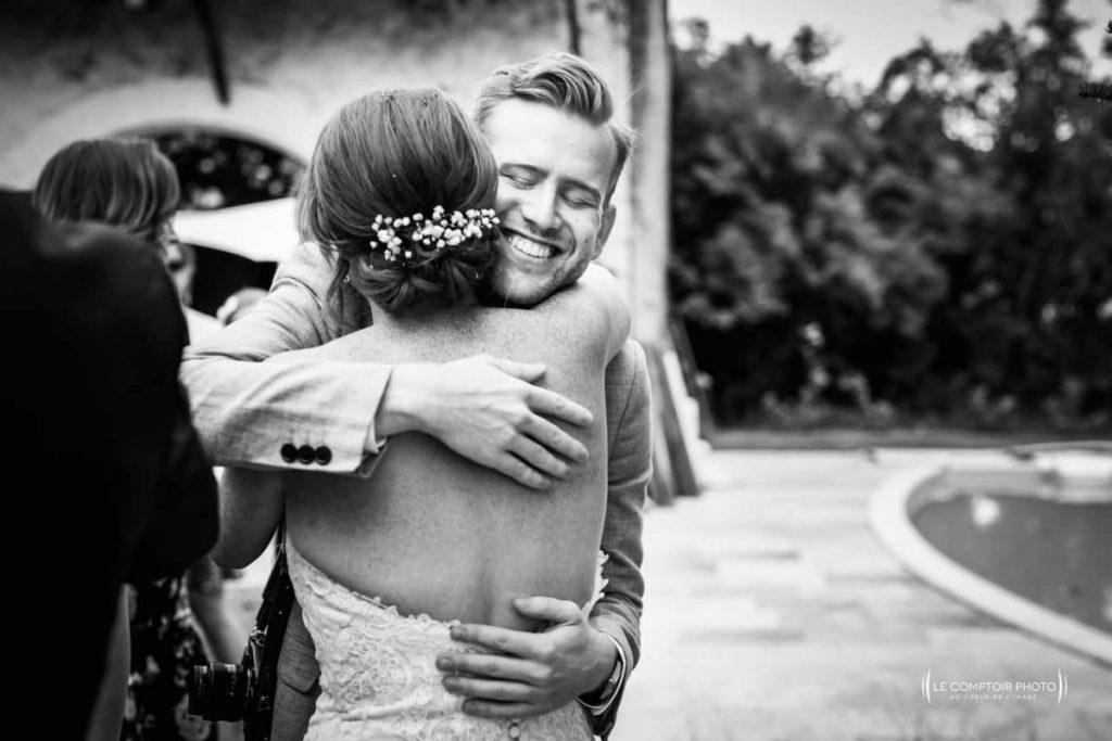Photographe mariage oise-Beauvais-Compiègne- Mariage franco-canadien-chateau lardier - ruch- bordeaux-libourne-ruch-aquitaine-gironde-émotion-naturelle-Le Comptoir Photo-embrassade d'un invité-mariée