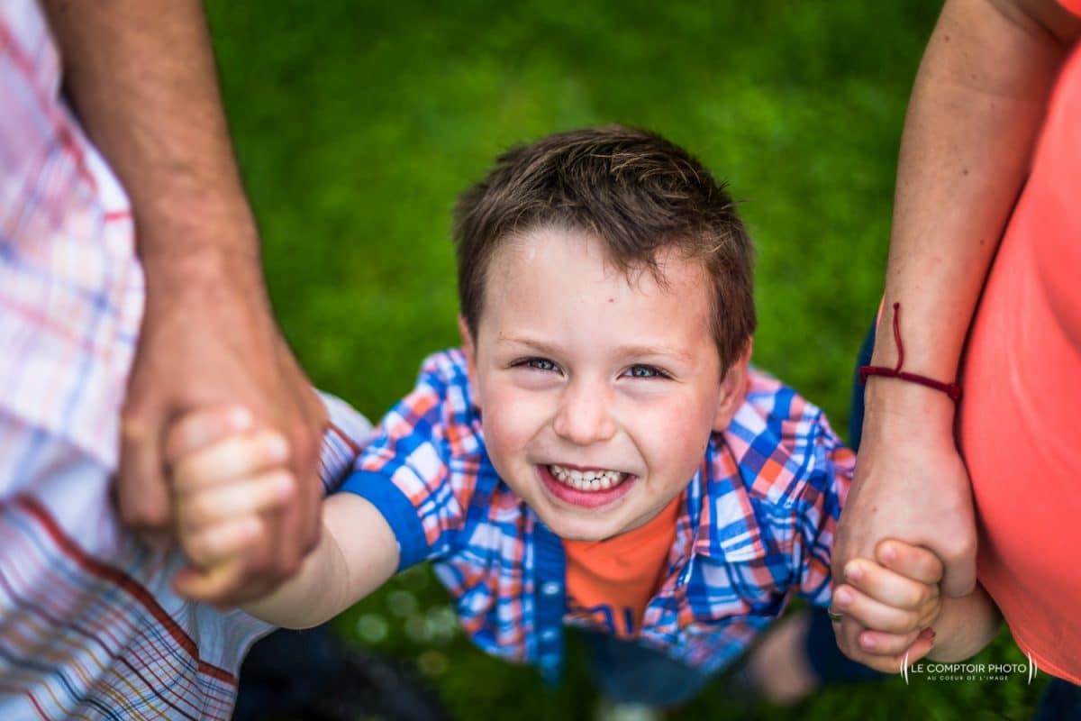 """alt= """" Seance-photo-portrait-enfant_exterieur_sourire enfant_bras des parents_Beauvais_Le-Comptoir-Photo """""""