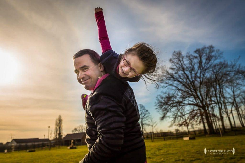 """alt= """" Seance-photo-portrait-enfant_exterieur_sourire enfant_bras des parents_Beauvais_parent portant enfant riantLe-Comptoir-Photo """""""