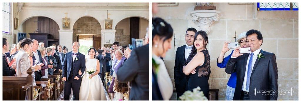 Entrée des mariés à l'église devant leurs invités - parents avec leurs téléphones - Mariage-Carolina-Fabien-Manoir-de-Chantilly_Gouvieux_Photographe-mariage-Oise_photographe-oise_Le-Comptoir-Photo