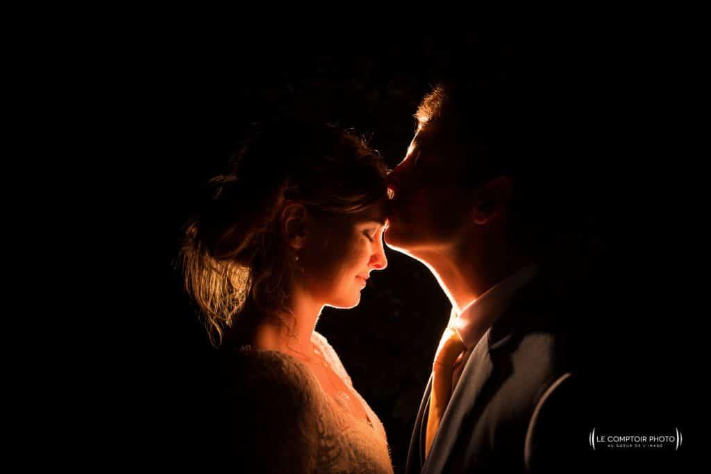 tendresse durant la séance couple de photo de nuit avec les mariés en Bretagne